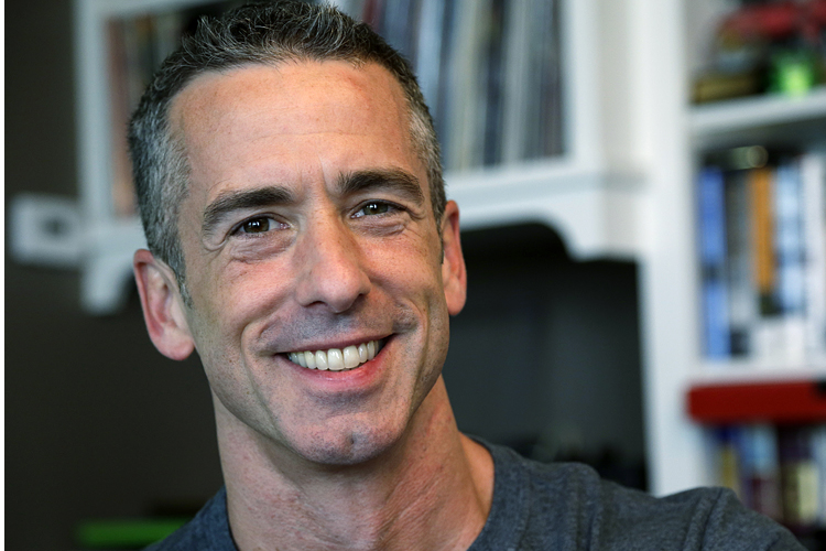 "In this photo taken on May 22, 2013, author Dan Savage is in his home in Seattle. Savage's latest book, ""American Savage,"" was released on Tuesday, May 28. (AP Photo/Elaine Thompson)"